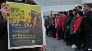An unidentified woman holds the newspaper advertisement, as a group of mainlanders pose for a picture in the background on 1 February 2012