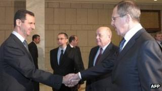 Syrian President Bashar al-Assad (L) shakes hands with Russian Foreign Minister Sergei Lavrov (R)
