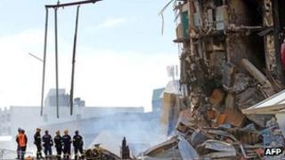 Rescuers stand at the smoking ruins of the CTV building in Christchurch, New Zealand on 24 February, 2011