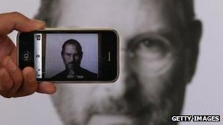 A photographer takes a picture with his own iPhone of a Steve Jobs tribute in London, United Kingdom in 6 October 2011