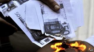 Man burning 50 euro notes (actually photocopied notes)
