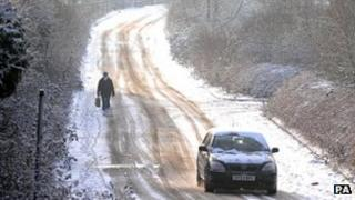 A woman walks along a snow covered road in Sixfields, Northampton, following overnight snow