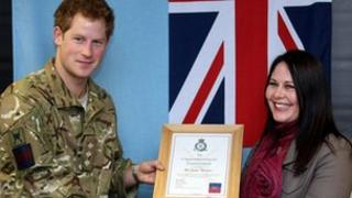 Prince Harry presents Jacqui Thompson with an award at RAF Honington