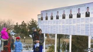 Residents look at a presidential election poster depicting the candidates in Ashgabat, Turkmenistan