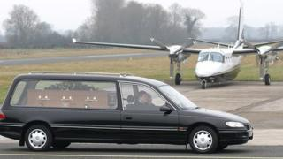 Bob Jones's coffin is driven past a plane