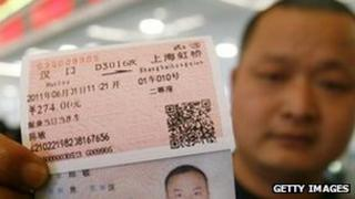 A passenger shows his real-name train ticket at Hankou railway station in Wuhan, central China, 23 May 2011