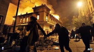 Greeks run past burning building in Athens, 12 Feb 12