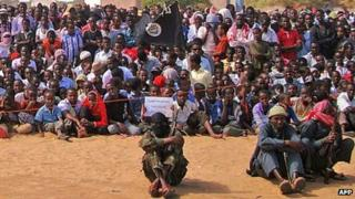 People watch Somali al-Shabab fighters on February 13, 2012, in Elasha Biyaha, in the Afgoei Corridor, during a demonstration to support the merger of al-Shabab and the al-Qaeda network