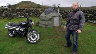 Ed Gold with his motor bike outside his yurt home