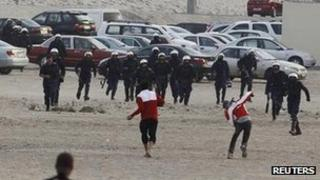 A protester throws a rock at riot police near Farooq Junction, formally known as Pearl Roundabout, west of Manama (13 February 2012)