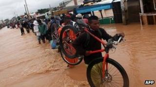 People cross a flooded road in the Sabotsy Namehana commune, north of Antananarivo on 14 February 2012 after Cyclone Giovanna hit Madagascar