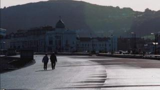 Couple stroll on Llandudno promenade