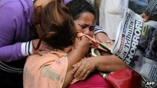 Women cry while they wait to recover the remains of a relative, killed during Comayagua prison fire, at the Forensic Department in Tegucigalpa on 16 February 2012