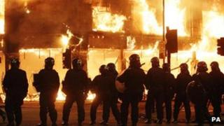 Police stand in line as fire rages through a building in Tottenham, during the riots on 7 August.