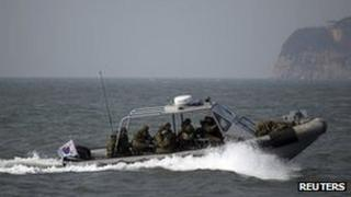 South Korean naval personnel go on a boat patrol near Yeonpyeongdo island as South Korean marines conduct live fire exercise on the island in Ongjin county, off Incheon, west of Seoul February 20, 2012