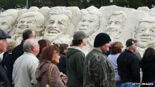 People in South Carolina look at sand sculpture depicting Republican presidential candidates (L-R): Mitt Romney, Newt Gingrich, former candidate Jon Huntsman, Rick Perry, Rick Santorum and Ron Paul