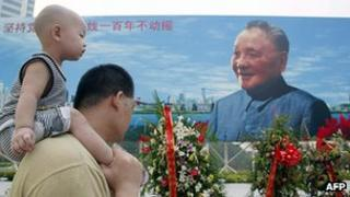 A father holds his son in front of a huge Deng Xiaoping billboard in Shenzhen, China (file photo)