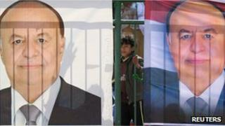 A boy stands between posters of Yemeni Vice President Abdrabbuh Mansour Hadi during an election rally in Sanaa