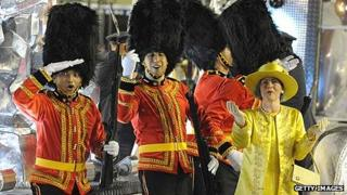 Carnival participants dressed as British guards and the Queen