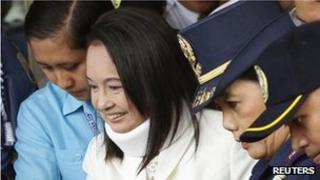 Former Philippine President Gloria Macapagal Arroyo escorted by policemen after attending her court arraignment in Pasay city, Metro Manila 23 February, 2012