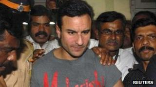 Bollywood actor Saif Ali Khan is escorted by police at a police station in Mumbai on 22 February 2012