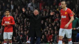 Alex Ferguson holds up his hands while Berbatov walks past him