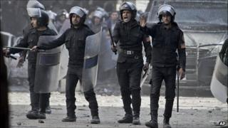 Line of riot police with shields, helmets and truncheons