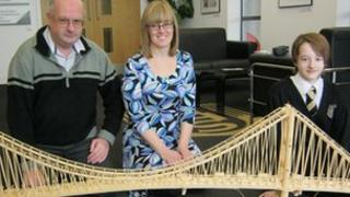 Three people standing behind the matchstick model of the Humber Bridge