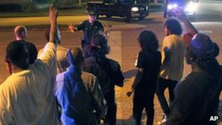 A police officer tries to control a group of people trying to get to their vehicles Orlando, Florida 23 February 2012