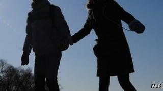 A couple hold hands while skating across a frozen lake at Shichahai in central Beiijng (file photo)
