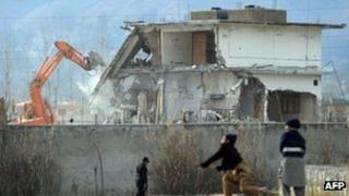 Young Pakistani boys play near demolition works on the compound where Al-Qaeda chief Osama bin Laden was slain last year in the northwestern town of Abbottabad on February 26, 2012.