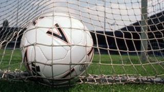Football resting against net