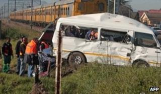 Rescuers at the scene of a collision between a minibus and a train, 26 August, 2010 file