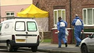 Forensic officers approach the house in Norris Green