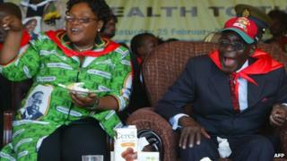 Zimbabwe's President Robert Mugabe (R) and the country's Vice-President Joice Mujuru eat cake as they attend a rally marking Mr Mugabe's 88th birthday in Mutare on 25 February 2012
