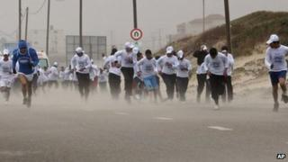 People compete in the Gaza marathon in strong winds