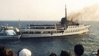 Bystanders watch the City of Poros cruise ship burning after the 1988 attack