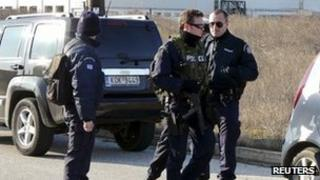 Police rush to secure an area around a factory where a man took two hostages in Komotini