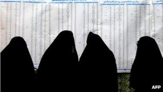 Iranian women look at a list of candidates at a mosque being used as a polling station in Tehran