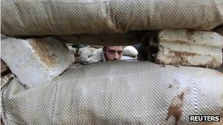 A Syrian soldiers looks through sandbags in Homs