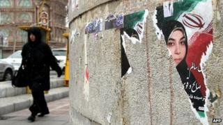 An Iranian woman walks past a torn electoral poster for a parliamentary candidate a day after the elections in Tehran on March 3, 2012