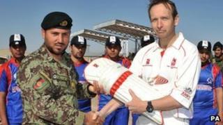 Lieutenant Colonel Tim Law presents cricket pads to RSM Saraj Udin