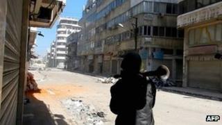 A man carries a Rocket Propelled Grenade (RPG) in the al-Hamidiya neighbourhood of Homs,