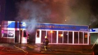 Firefighter attends blaze at car showroom
