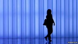 Business woman with bag against modern light wall blue