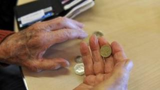 A pensioner holding some coins