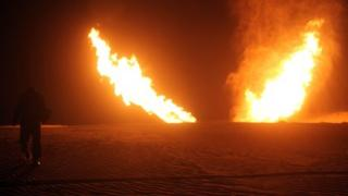 Two jets of flame apparently rise from the desert