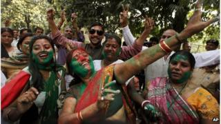 Samajwadi Party supporters dance with coloured powder on their faces as they celebrate an early lead of the party leader Mulayam Singh Yadav in Uttar Pradesh state election in Lucknow, India.