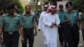 Bangladeshi policemen and Saudi officials inspect the area where a Saudi Arabian diplomat was shot dead in Dhaka