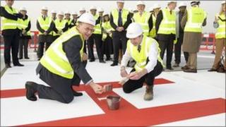 Hospital trust chief executive Andrew Morris and Adam Wells, construction director, finish painting the giant 'H' on the new helipad at Frimley Park Hospital
